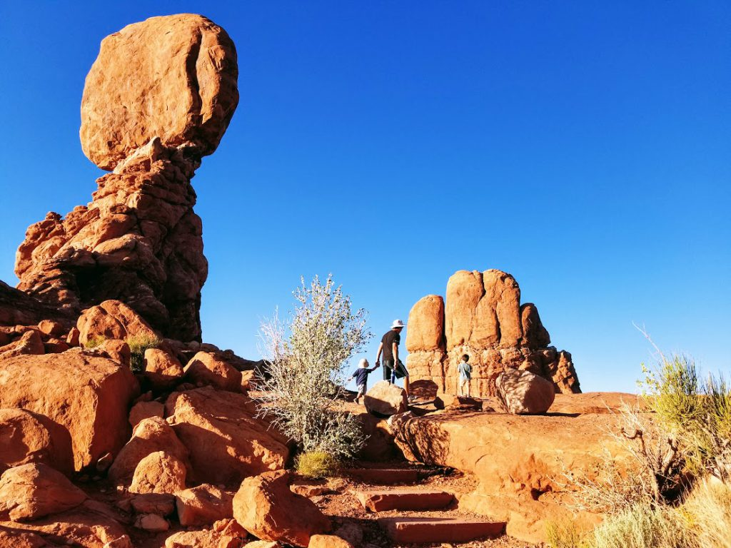 Family at Balanced Rock- Arches  National Park with kids