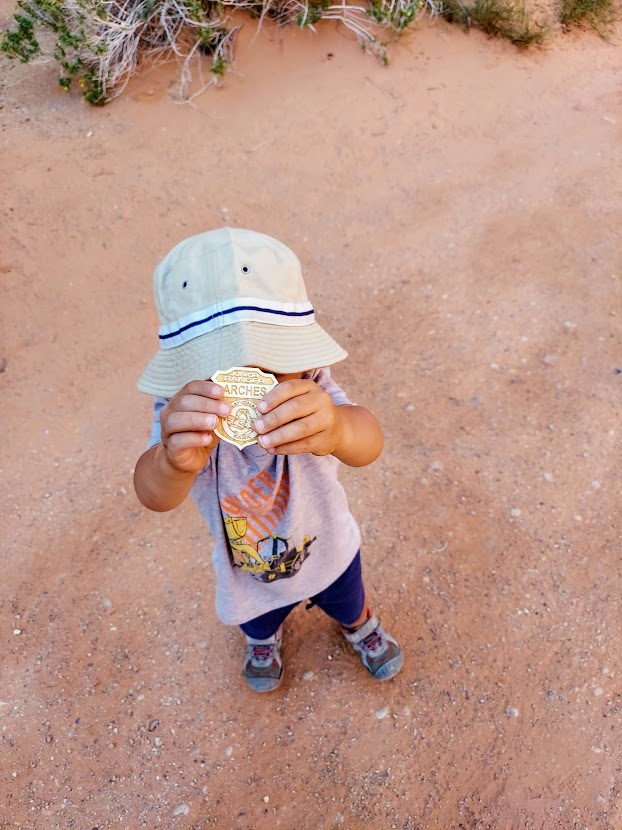 Child holding a Junior Park Ranger badge- Arches National Park with Kids