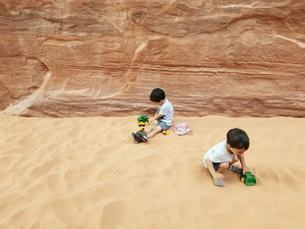 Kids playing with trucks in the sand- Arches National Park with Kids