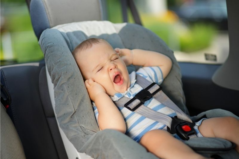 Baby yawning in a car seat- road tripping with a baby